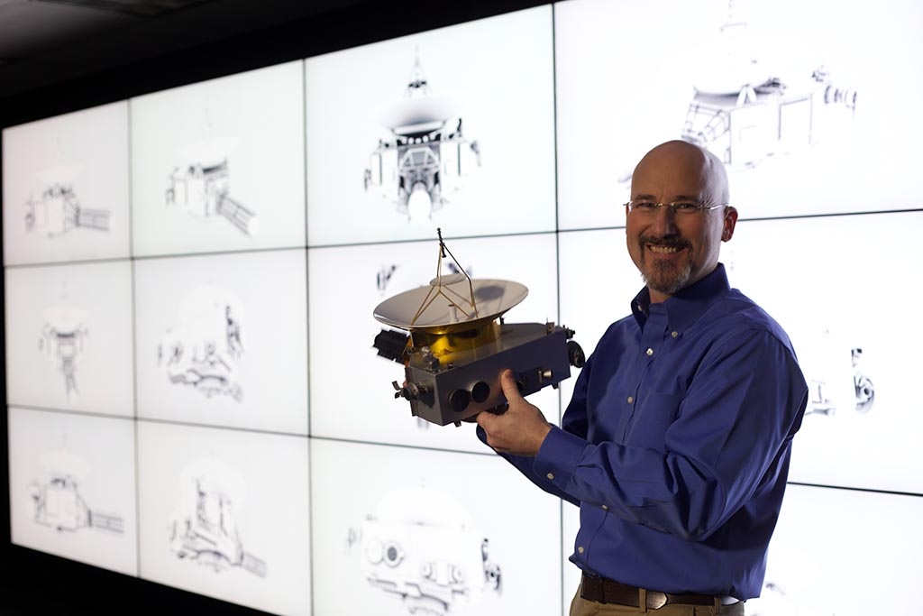 GREENBELT, MD.- With a scale model of New Horizons in his hands, Chris Hersman explains how the imagination of scientists met with the limitations of engineering to design the spacecraft. (Photo Credit: National Geographic Channels/Harriet Bailey)